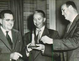 Image of Ben Tobin holding a statue of the Empire State Building alongside business partners Glancy and Stevens.